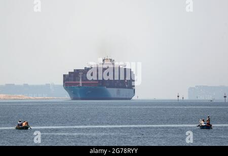 Fishermen travel on boats front of container ships passing through the Suez Canal in Ismailia, Egypt July 7, 2021. Picture taken July 7, 2021. REUTERS/Amr Abdallah Dalsh