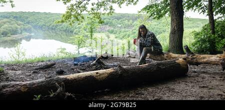 An attractive girl with a cup in her hand sits on a log and warms herself near a fire in the forest.