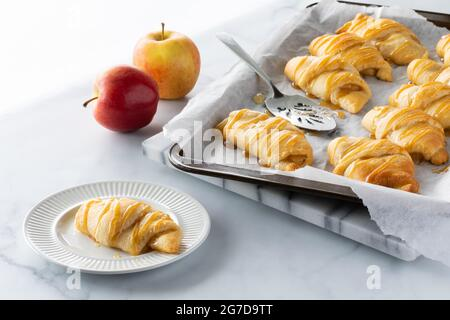 Apple filled crescent roll on a small plate with a baking sheet of more in behind, against a bright sunny window.
