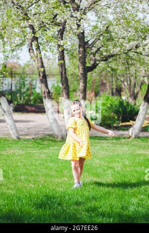 a laughing, smiling girl in a yellow dress circles around herself on the lawn in the backyard of a village house on a local trip with her family