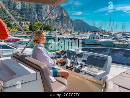 Beautiful blond woman driving yacht. Adult woman model in a white shirt sitting at the wheel of the yacht and begin to drive luxury boat from the port.