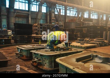 Unrecognizable workers with molds for metal cast in metallurgical plant foundry. Heavy industry.