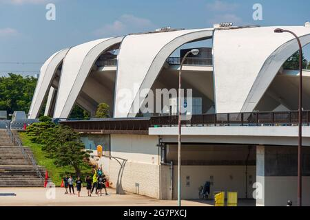 The Masachika Murata-designed athletics stadium in the background, young people play basketball inside Komazawa Olympic Park, Tokyo on 10 June 2021. The park was built for the 1064 Olympics and remains a popular leisure venue. Robert Gilhooly photo