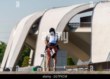 A man carries his son past the Masachika Murata-designed athletics stadium inside Komazawa Olympic Park, Tokyo on 10 June 2021. The park was built for the 1064 Olympics and remains a popular leisure venue. Robert Gilhooly photo