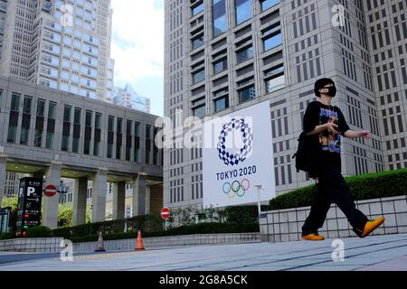 Tokyo, Japan. 16th July, 2021. A man wearing a face mask as a preventive measure against the spread of coronavirus walks past a banner for the upcoming Tokyo 2020 Olympics in front of the Tokyo Metro Government building. (Credit Image: © James Matsumoto/SOPA Images via ZUMA Press Wire)
