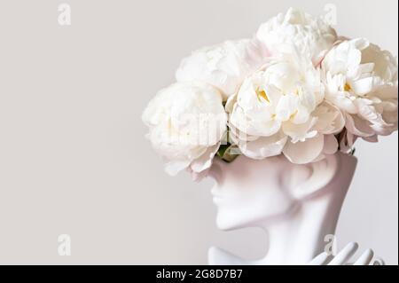 Bunch of white peonies in human head vase