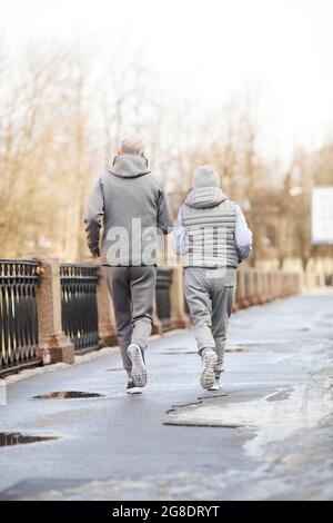 Full length back view at active senior couple running outdoors in winter
