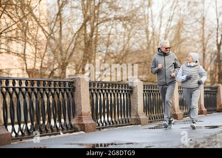 Full length wide angle view at active senior couple running outdoors in winter