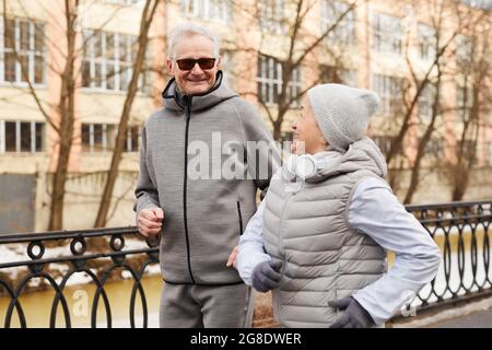 Waist up portrait of active senior couple jogging outdoors in winter and smiling happily, copy space