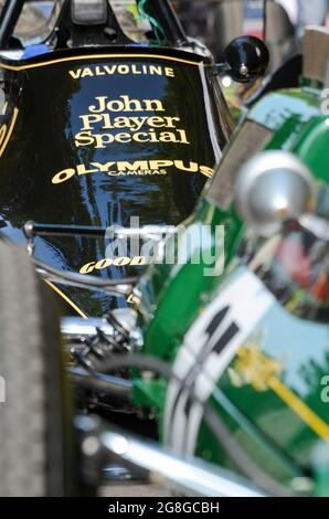 Detail of a 1970s Lotus 79 with John Player Special sponsorship behind a 1960s vintage green Lotus at the Goodwood Festival of Speed event, UK