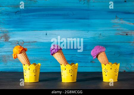 Three ice cream cones on old wooden blue background. The scoops are assorted of blueberry,  strawberry and apricot icecream in waffles