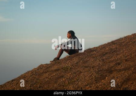 Uribia, La Guajira, Colombia - May 28 2021: Young Latin Brown Man with Braids on his Head Sits Pensively Waiting for the Sunset in the Desert