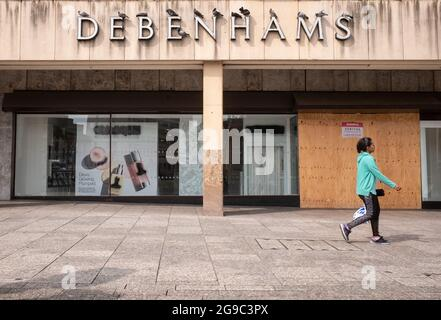 Closed and boarded up branch of Debenhams department store, with pigeons roosting on the sign
