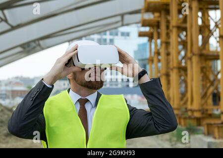 Mature engineer looking the future project through the virtual reality glasses while standing on construction site