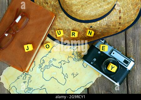 Straw hat, book, camera and glasses with word Journey on world map and wooden planks background