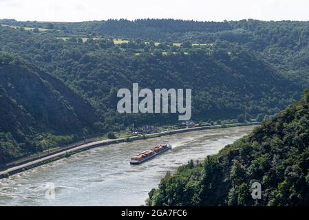 Loreley, Germany - 25 July 2021. A large barge carrying a lot of containers on the Rhine River in western Germany, visible hills overgrown with trees.