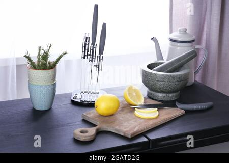 Sliced lemon and tableware on kitchen table, close up