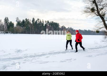 Smiling senior couple jogging in snowy winter park. Elderly wife and husband doing workout outdoors. Active lifestyle concept.