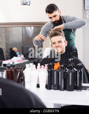 male hairdresser doing haircut for male client at hair salon