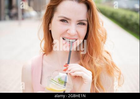 Young beautiful red-haired woman with braces drinks cooling cocktail outdoors in summer. Portrait of a smiling girl with freckles