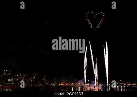 Heart shaped fireworks sideways over a city skyline at night. Other fireworks rise towards the heart.