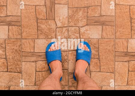 Male feet in blue house slippers stand on brown tile floor with abstract stone pattern texture background, top view.