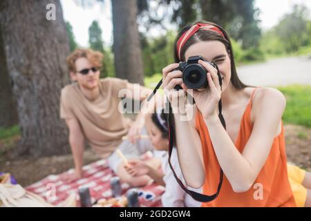 Girl looking into camera lens and friends behind