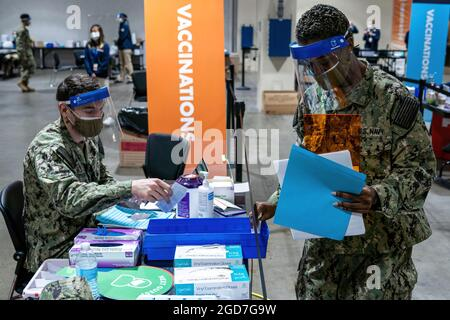 U.S. Navy Hospitalman Matthew Tuten (left), a native of Wichita Falls, Texas, and U.S. Navy Hospitalman Kenecha Campbell (right), a native of Orlando, Florida, assigned to Naval Medical Center Portsmouth, Virginia, refill COVID-19 vaccine supplies at their assigned stations at the Hynes Convention Center COVID-19 Community Vaccine Center in Boston, April 2, 2021. U.S. Navy Sailors from across the country are deployed in support of Department of Defense federal vaccine response efforts. U.S. Northern Command, through U.S. Army North, remains committed to providing continued, flexible DoD suppor