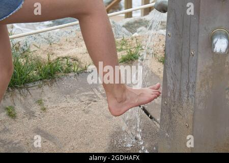 close-up of feet of a girl washing the sand from the beach in a shower on the coast