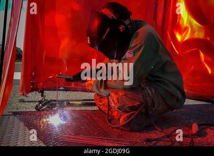 U.S. Air Force Airman 1st Class Mason Hughes, 633rd Civil Engineer Squadron structural journeyman, welds a pit plate closed at Joint Base Langley-Eustis, Va., Dec. 4, 2019. Pit plates are covers that protect water valves around the installation and are welded down for safety. (U.S. Air Force photo by Tech. Sgt. Carlin Leslie)