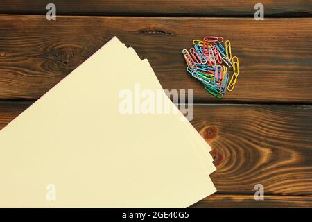 Stationery clips and paper on wooden background