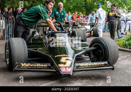 Classic Lotus 79 Formula 1, Grand Prix racing car at the Goodwood Festival of Speed motor racing event 2014. Classic Team Lotus crew pushing car