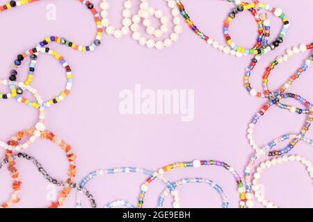 Necklaces and bracelets made from beads and pearls on a purple background. Border frame with copyspace.