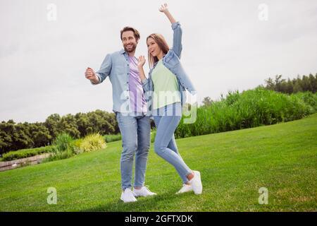 Full size photo of good mood cheerful couple dancing having fun enjoying free time active energetic weekend