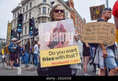 London, United Kingdom. 28th August 2021. An activist holds an anti-McDonald's placard outside Smithfield Market during the National Animal Rights March. Animal rights activists and organisations marched through City of London demanding an end to all animal exploitation. (Credit: Vuk Valcic / Alamy Live News)