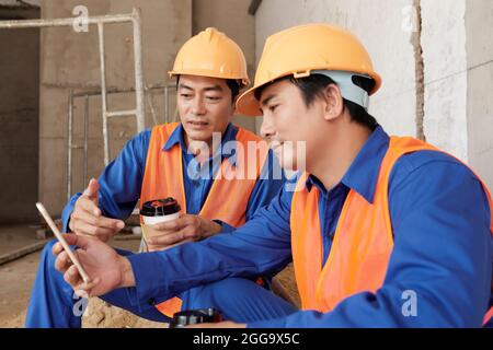 Construction workers in uniform and hardhats discussing new meme on social media when having coffee break