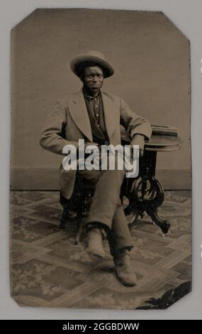 Untitled (Portrait of a Seated Man), 1880. Black-and-white portrait photograph of seated dark-skinned man in a light-colored jacket on a patterned carpet, left arm resting on a small table.