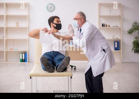 Young patient visiting old doctor in vaccination concept