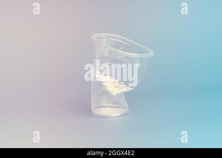 Crushed disposable glass on a gradient pink blue background. Recycling concept.
