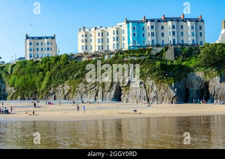 Colourful buildings on the headland above The South Beach at Tenby in Wales seen at low tide.