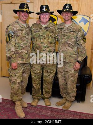 Retired Col. Bruce Crandall (center), a Medal of Honor recipient, poses for a picture with Col. John Novalis, from Williamsport, Pa., (right) commander of the 1st Air Cavalry Brigade, 1st Cavalry Division, and Command Sgt. Maj. Glen Vela, the brigade's senior enlisted adviser March 28. Crandall was awarded the Medal of Honor for his actions as a UH-1 Huey pilot on the day of Nov. 14, 1965 in Vietnam. That day, he flew his helicopter into landing zone x-ray 22 times, withstanding enemy fire and a continuous threat from the north Vietnamese as he helped provide ground troops with needed supplies