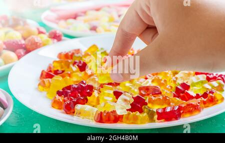 Hand takes colorful gummy bears candies of the plate. Close-up. Jelly treats for children and adults.
