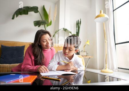 Mother helping her son to do homework for school Spbi. Child writing notes in notebook, mom helping attendance. together, studying, learning concept.