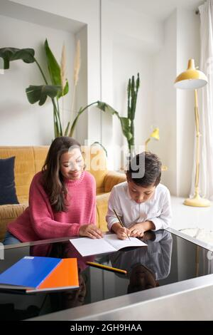Vertical photo. Mother helping her son with his homework in the living room at home.