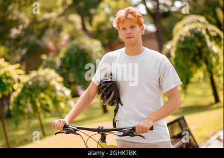 Guy with bike and helmet standing resting