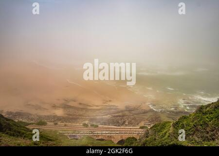 The view of Kaaiman's River Beach with railway bridge during misty morning at Wilderness in the Garden Route of Western Cape, South Africa.