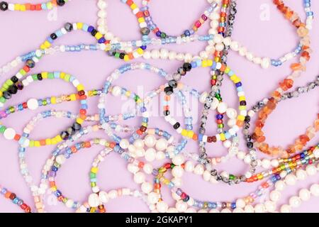 Necklaces and bracelets made from multicolored beads and pearls on a purple background.