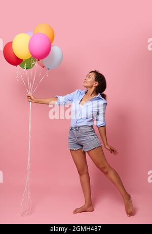 Full length body size view of gorgeous stunning cheerful glad wavy-haired mixed race African lady holding in hand bunch air balls corporate event orga