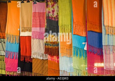 Brightly coloured fabrics on street market stall Florence Italy JMH0853 - Stock Photo