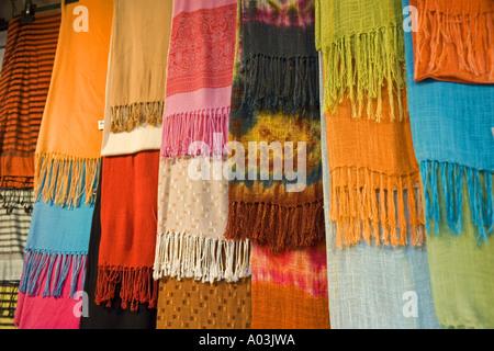 Brightly coloured fabrics on street market stall Florence Italy JMH0854 - Stock Photo